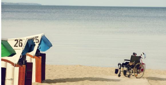 Fauteuil roulant vide sur la plage face à des cabanons